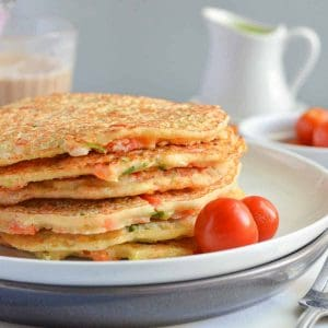 close up of stacked pancakes with baby tomatoes
