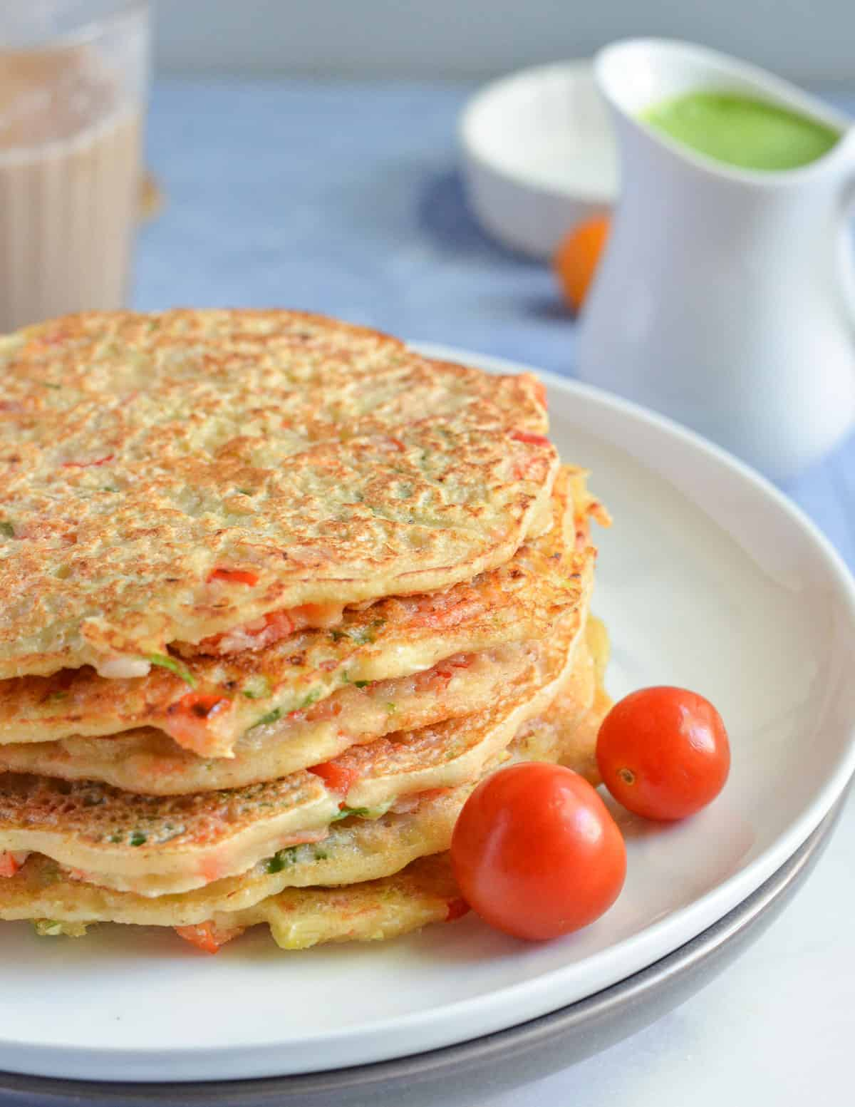 pancakes are stacked up in white plate with baby tomato