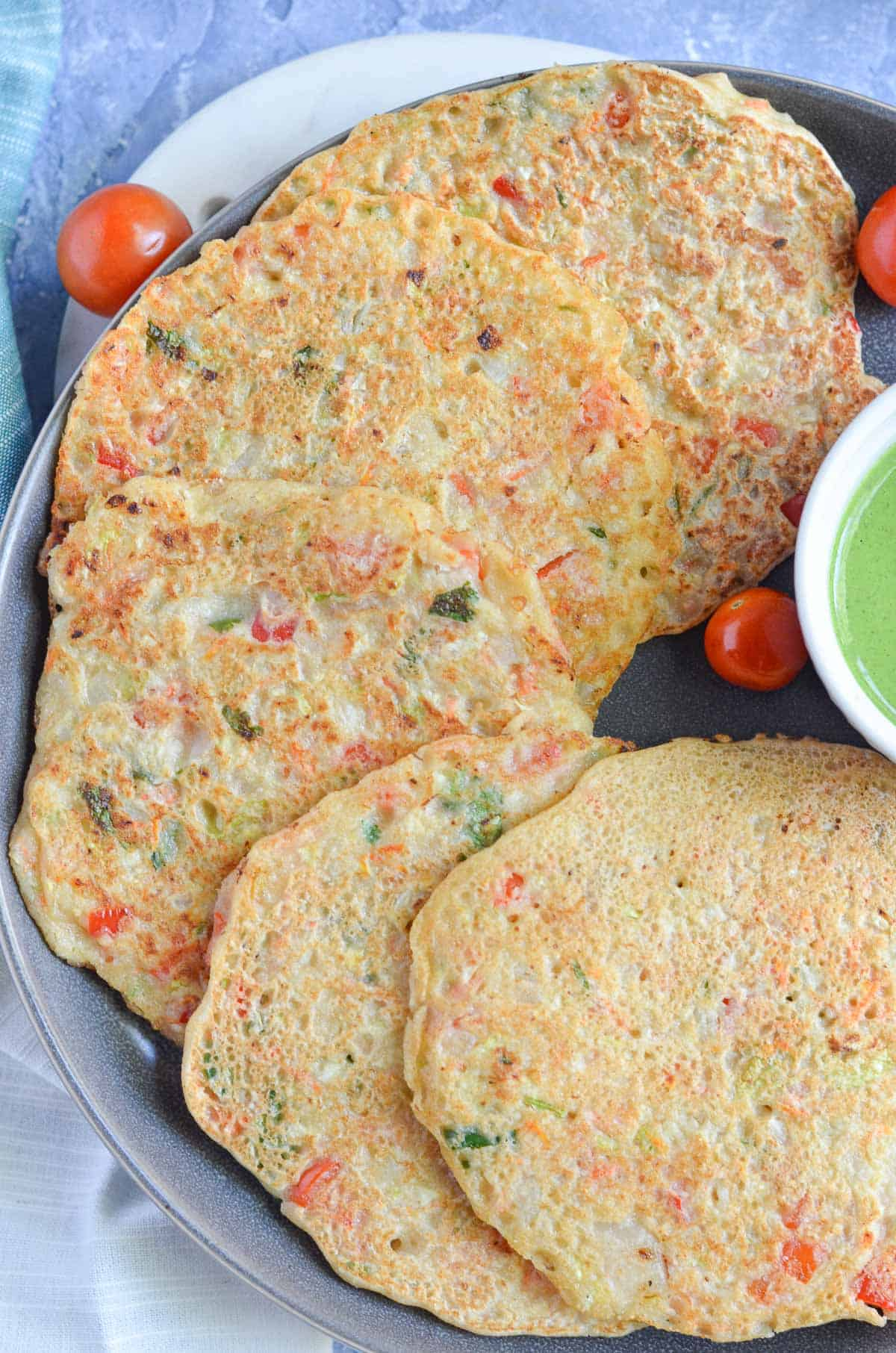 vegetable pancakes served in black plate with tomatoes & green chutney.