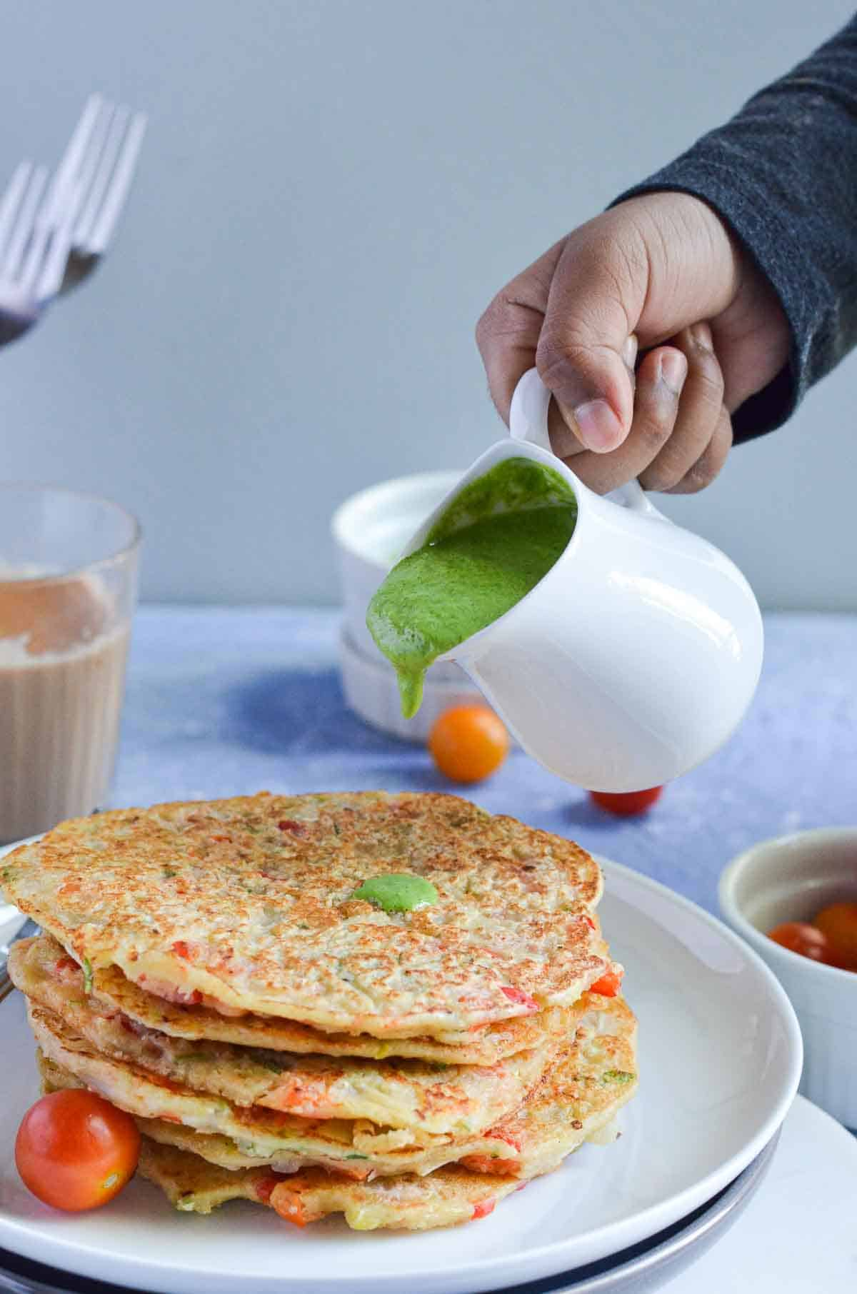 green chutney poured over a stack of savory pancakes