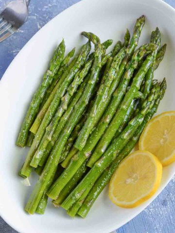 seasoned asparagus served in white oval shaped bowl with lime wedges