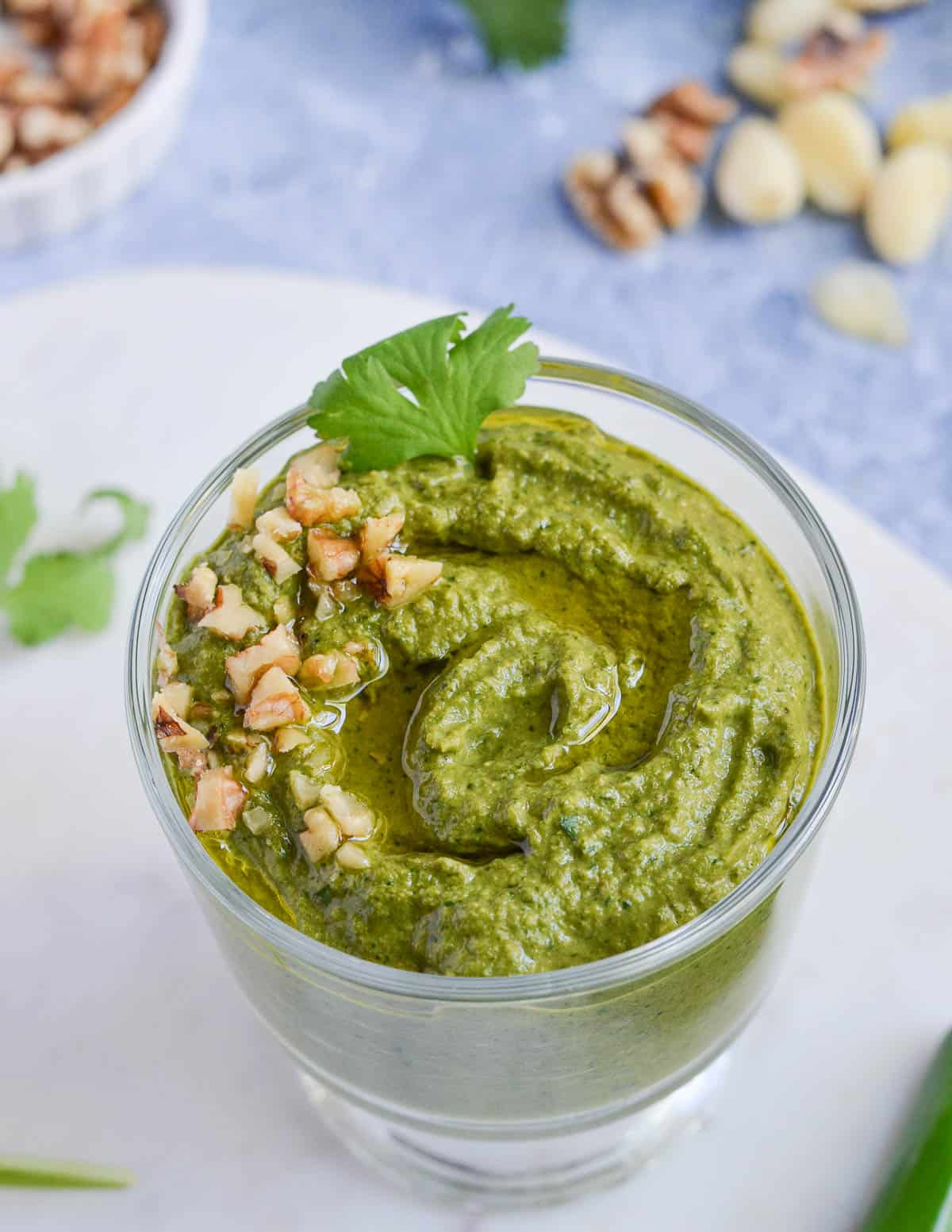 poblano pesto served in a glass and garnished with walnuts