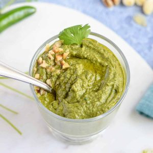 poblano pesto shown with a spoon in a glass jar