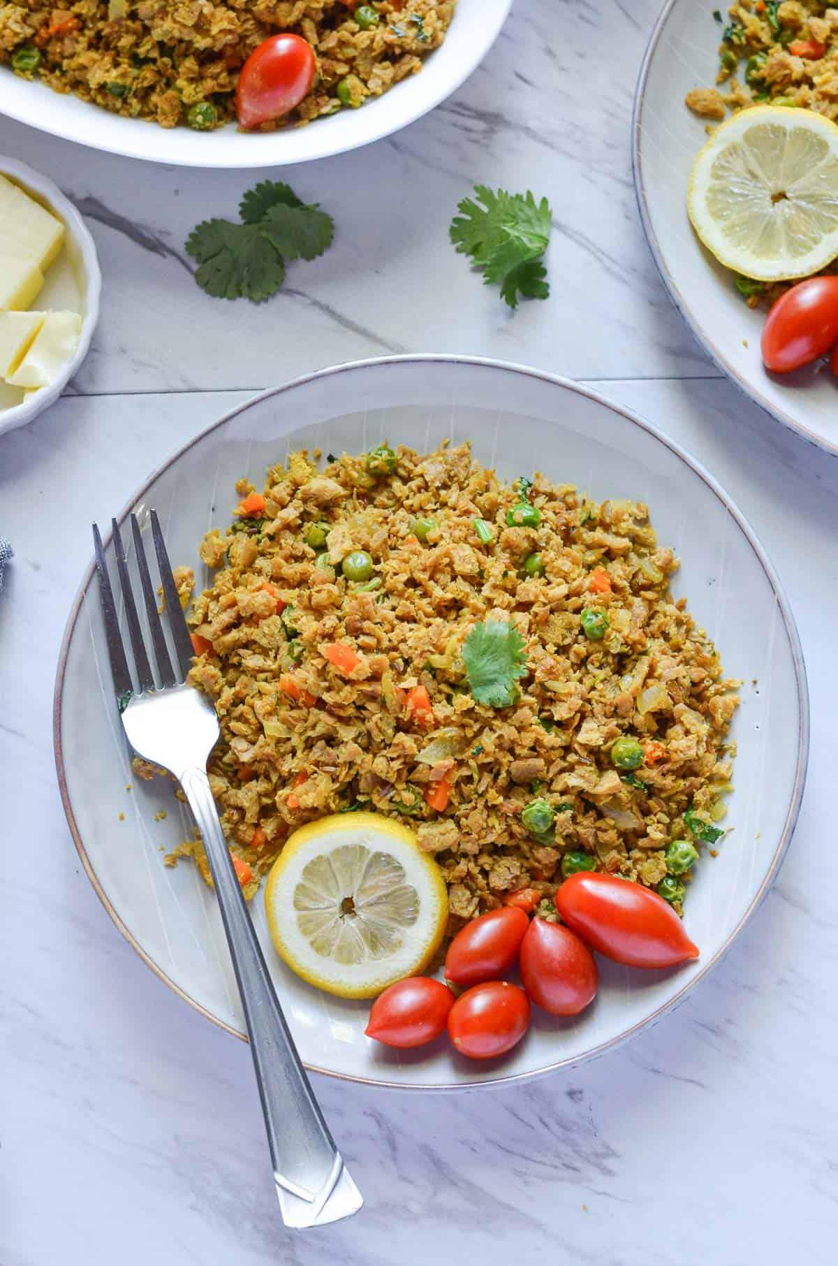 veggie scramble is served with tomatoes, lemon wedge & fork.