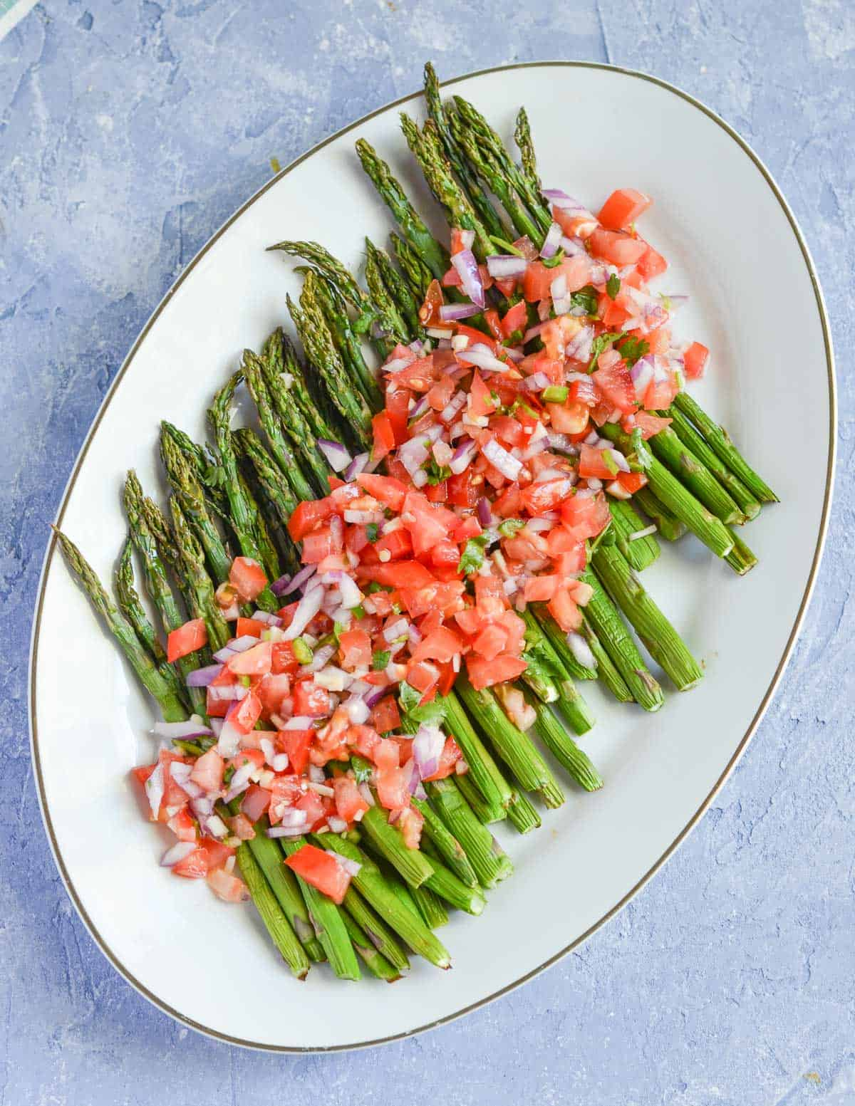 roasted asparagus served in a oval platter with pico de gallo.
