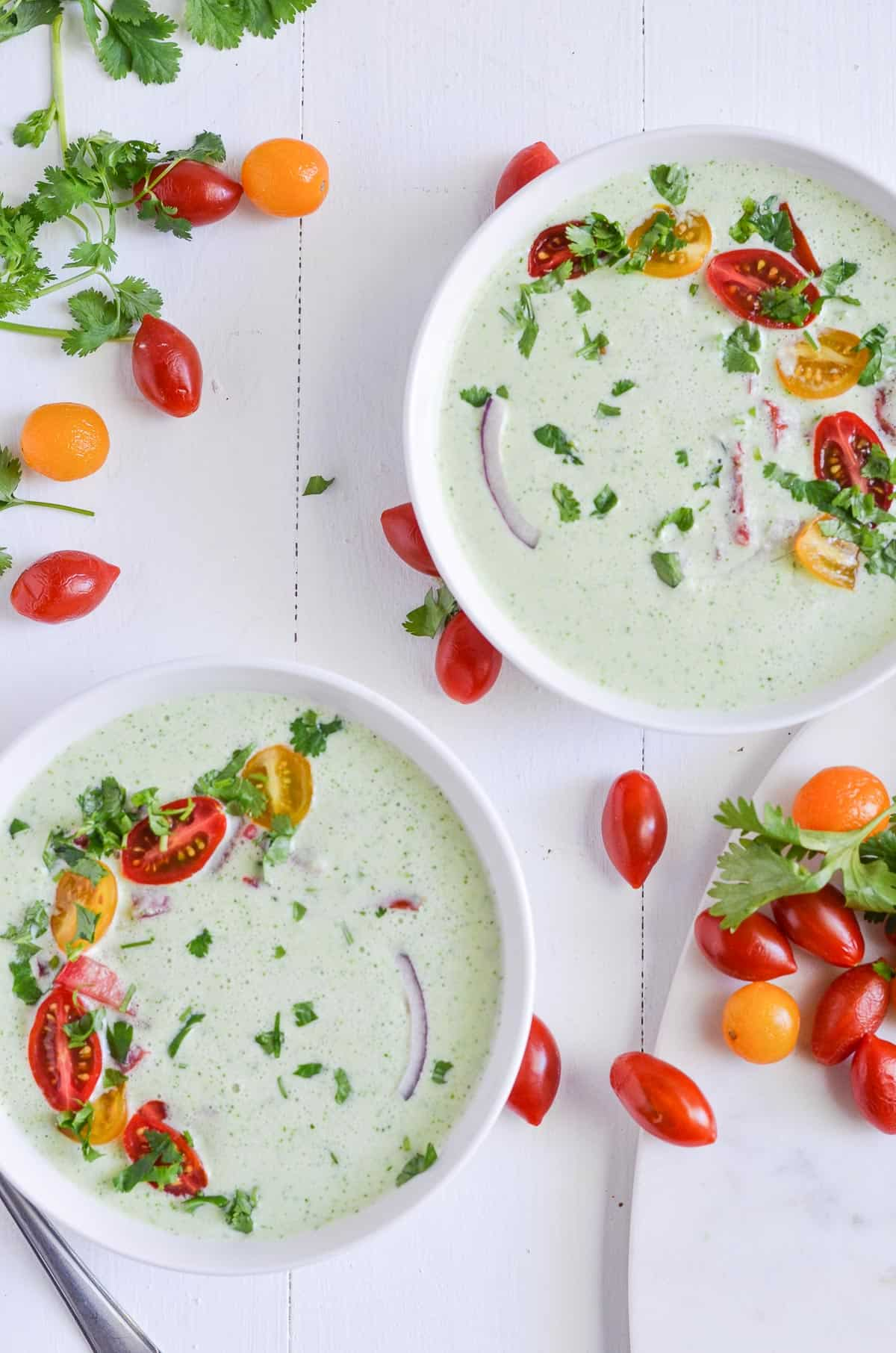 two bowls of chilled cucumber soup, garnished with cilantro & cherry tomatoes.