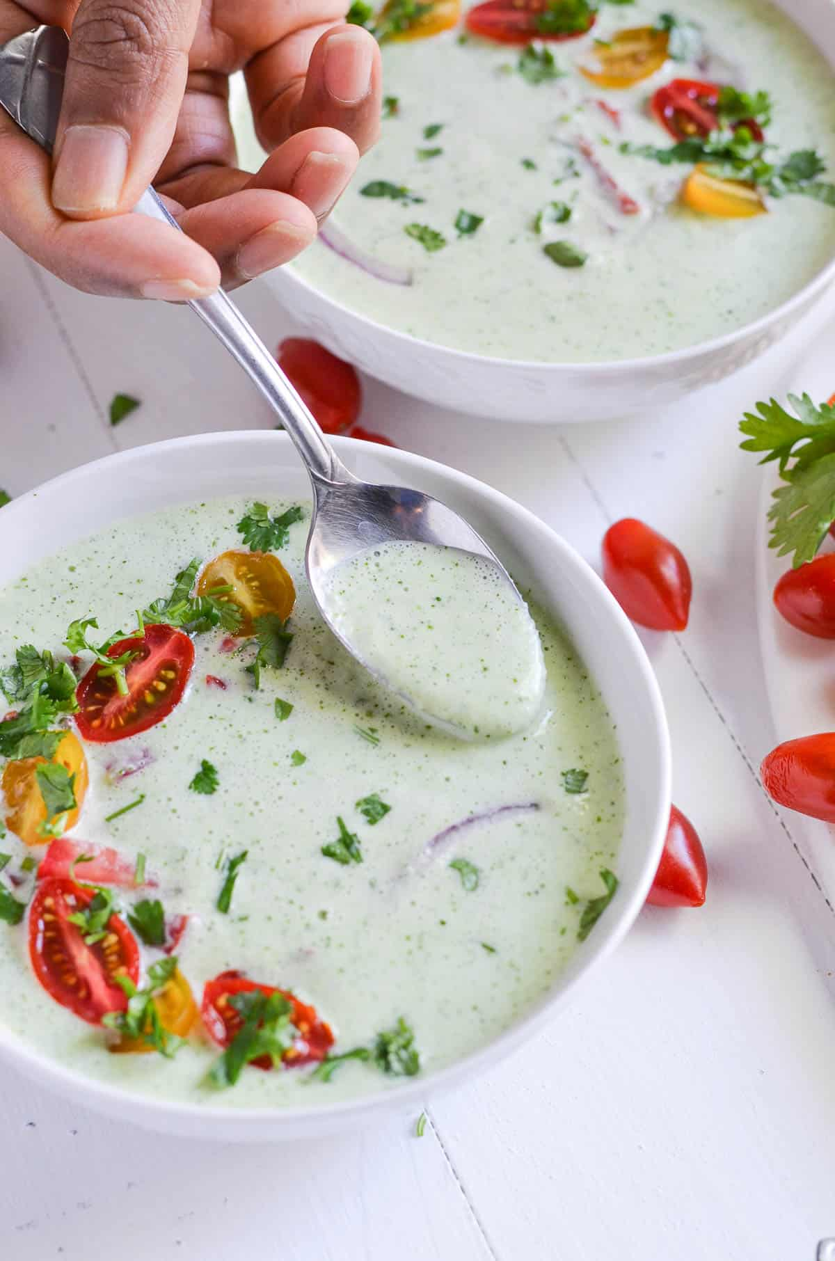 A spoonful cucumber soup is showcased to show the texture.