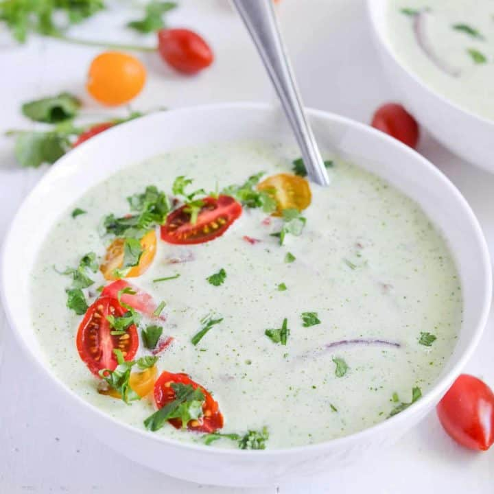 A close up of cucumber soup bowl with the spoon.