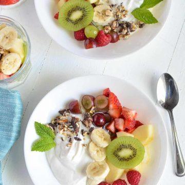 fruit salad bowl with greek yogurt garnished with min leaves & granola