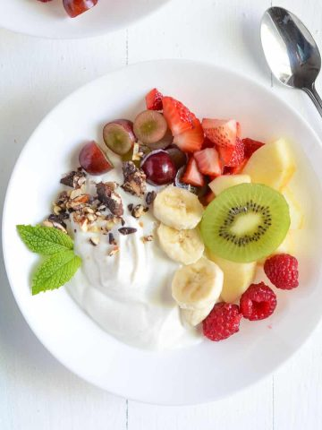 greek yogurt fruit salad served in white plate with mint garnish