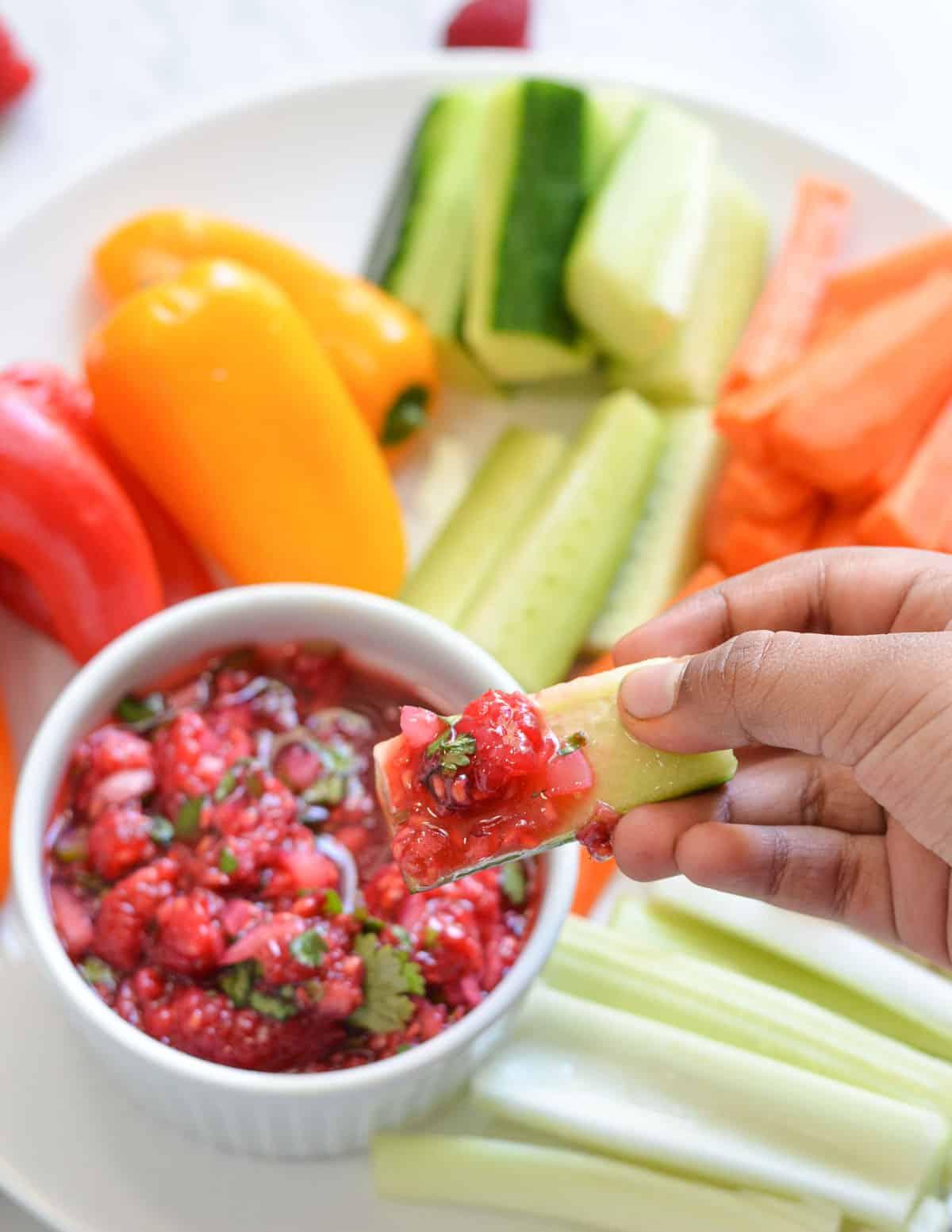 a bite size cucumber dipped in salsa