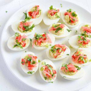 a close up of garnished masala deviled eggs