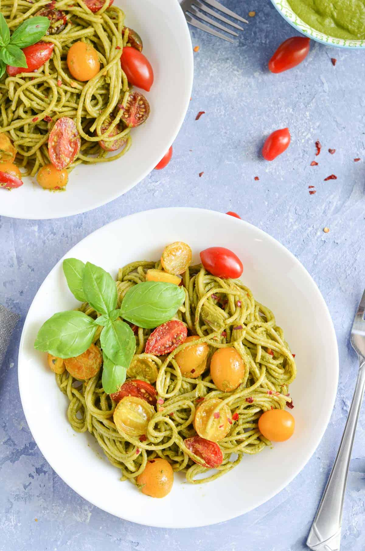 overhead click of pesto pasta garnished with cherry tomatoes & basil leaves