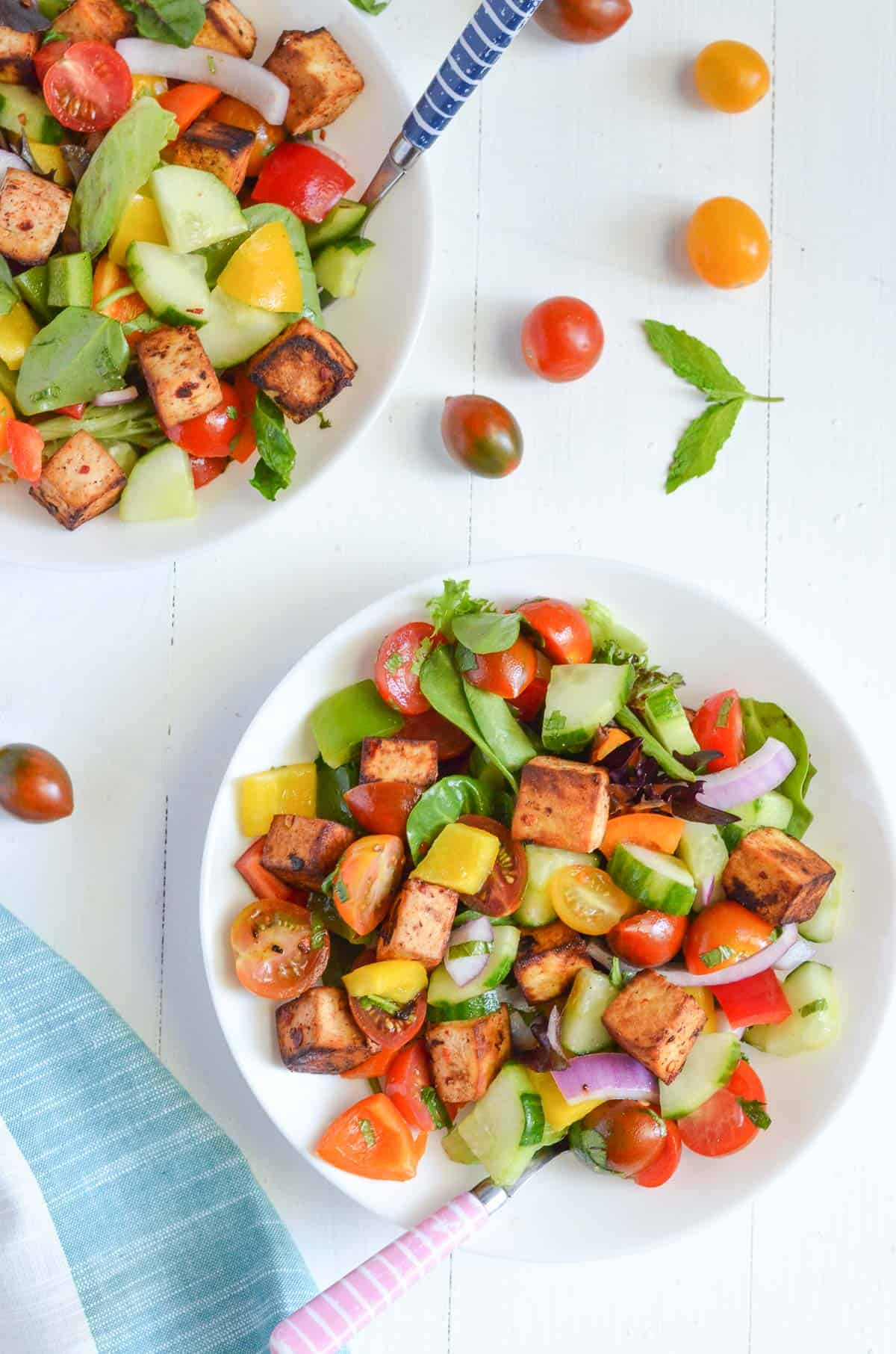 tofu panzanella salad is served in white plates