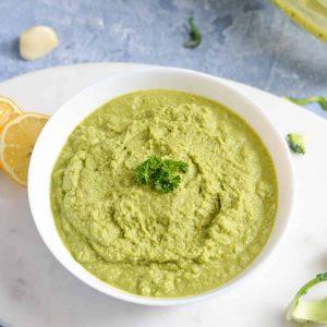 close up of broccoli pesto in a white bowl