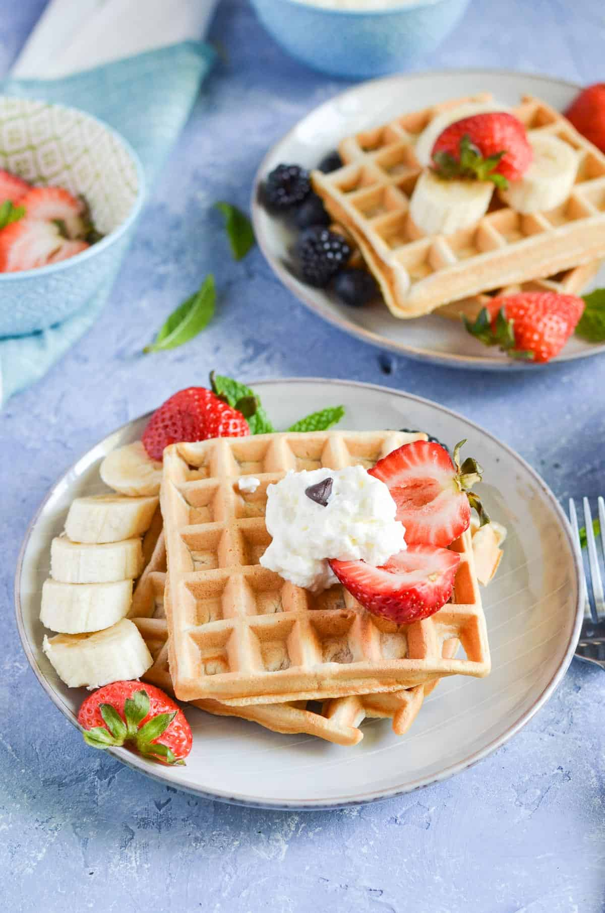twp plates shown with waffles. served with banana, maple syrup, cream and berries.