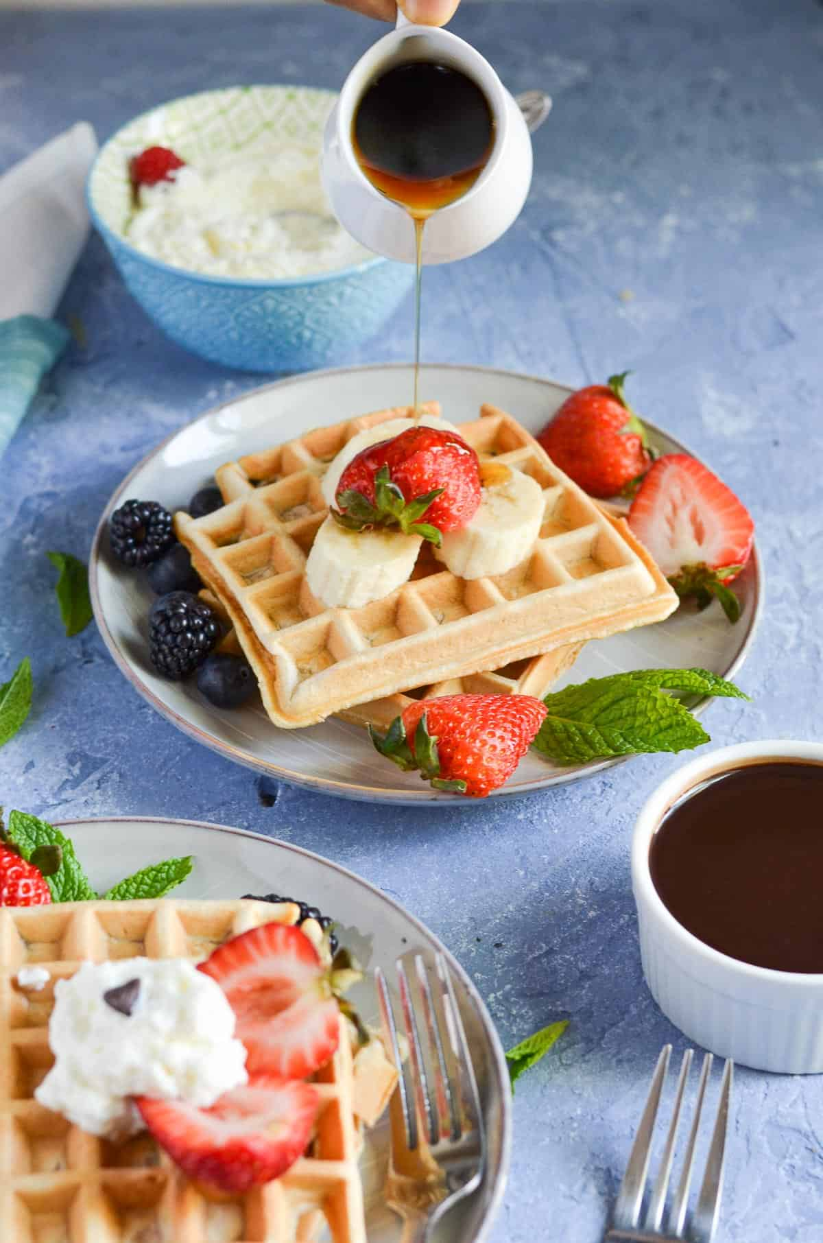 maple syrup is poured over wheat waffles.