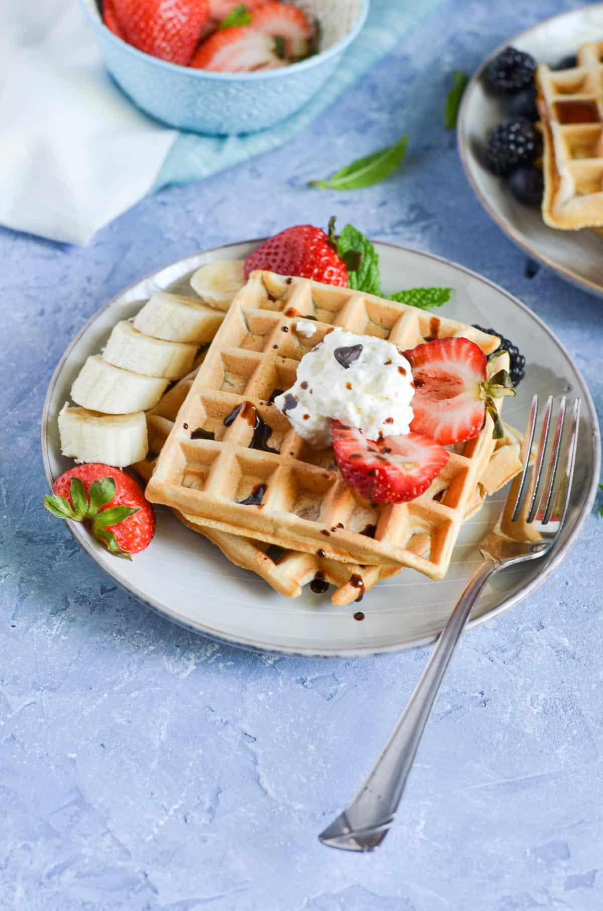 close up click of waffles served in a plate with fork.