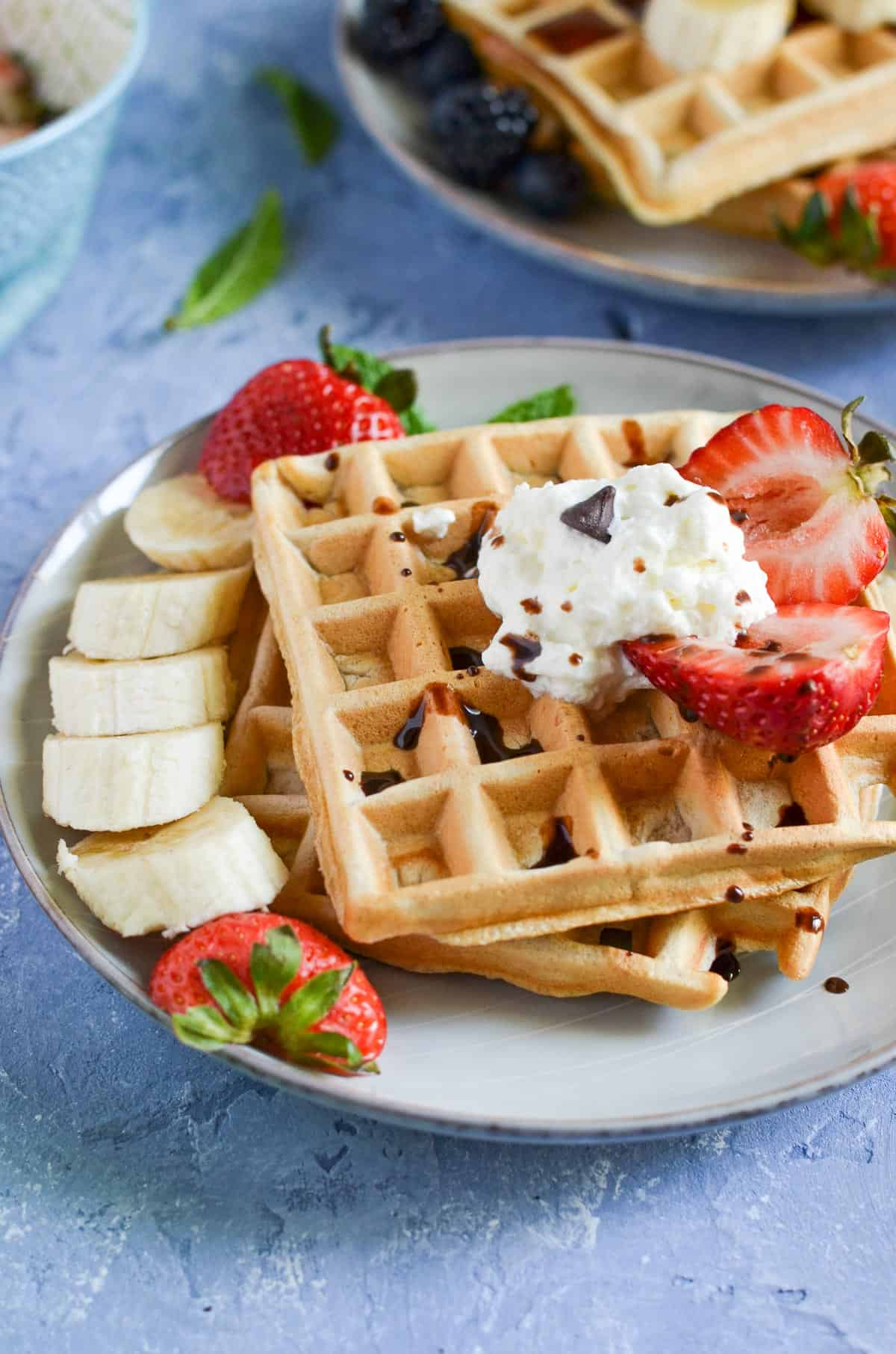 close up of waffles served with whipped cream, banana, berries and chocolate syrup.