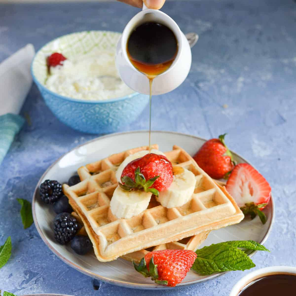 close up click of wheat waffles served with berries, banana and maple syrup.