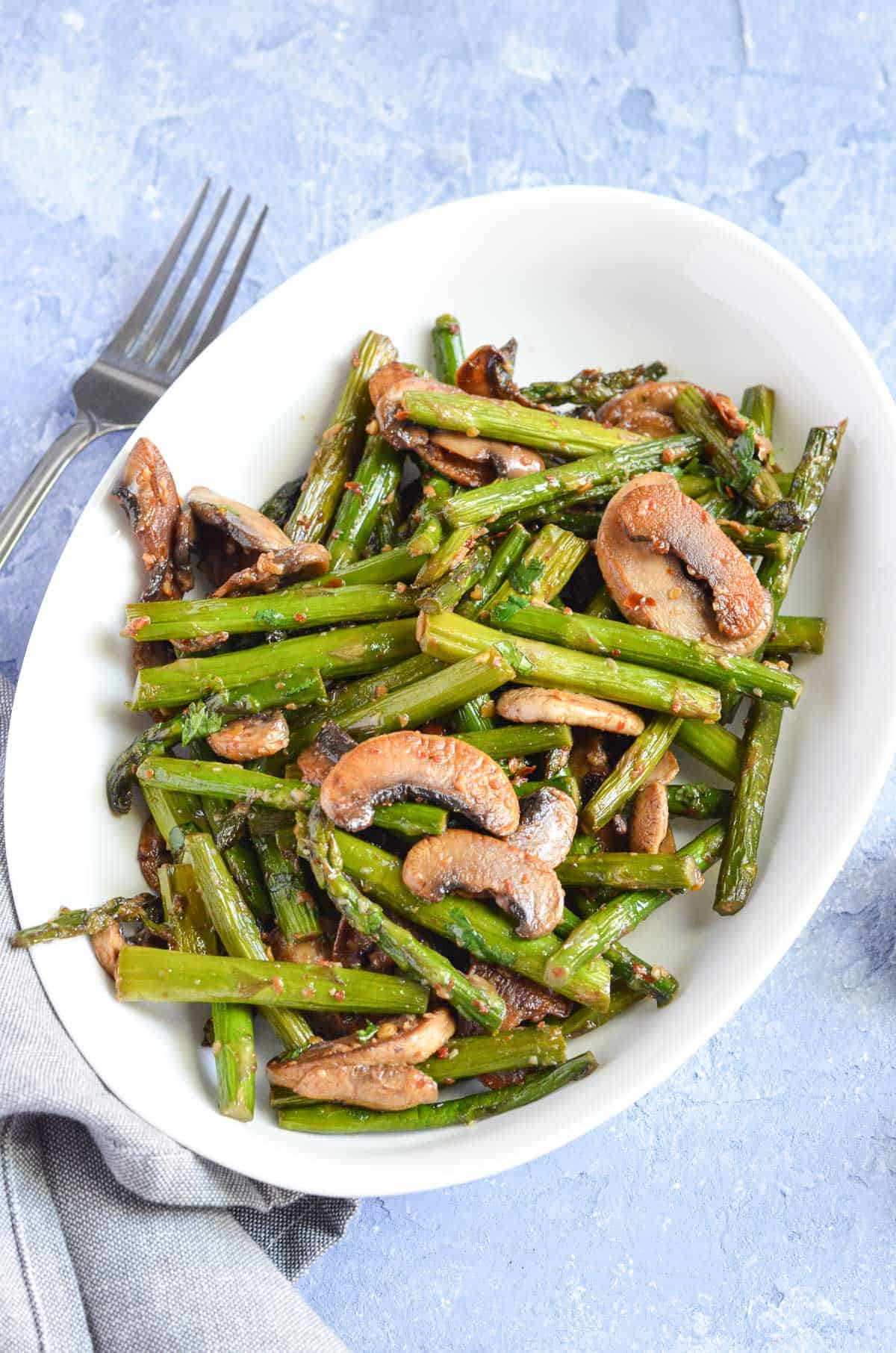 mushrooms & asparagus served in white oval bowl along with fork.