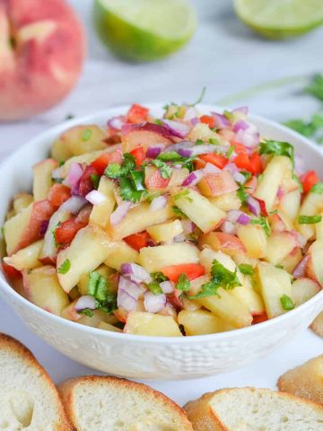 close up of peach salsa served with baguette slices.