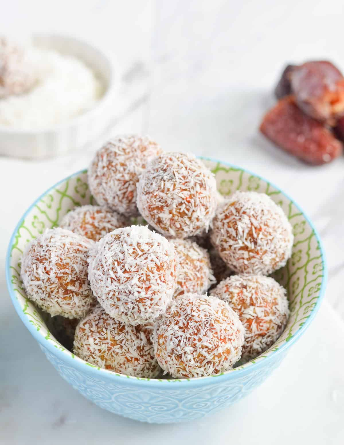 close up click of bliss balls, dry coconut & dates are behind the bowl.