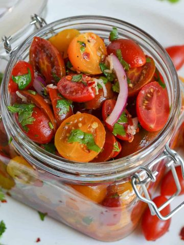 close up of marinated tomatoes in the glass jar.