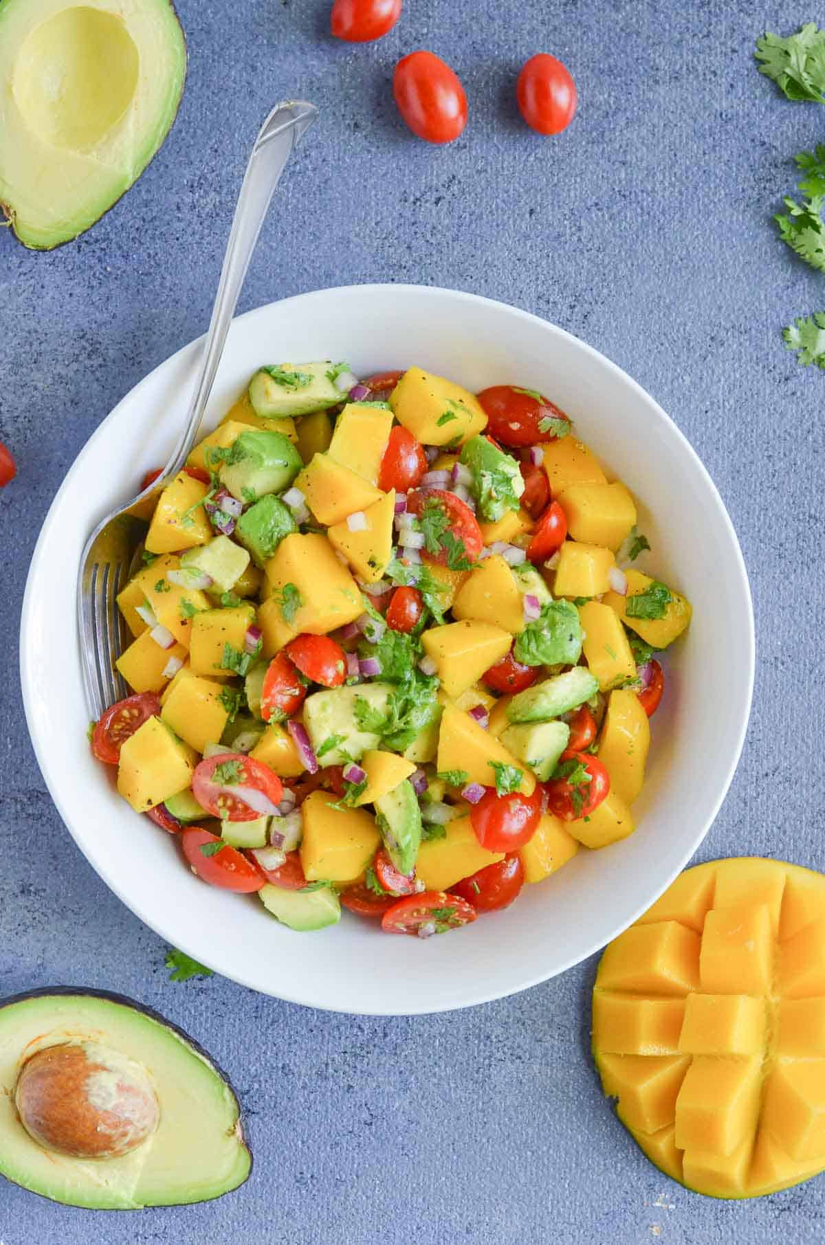 overhead click on avocado mango salad in white bowl along with the fork.