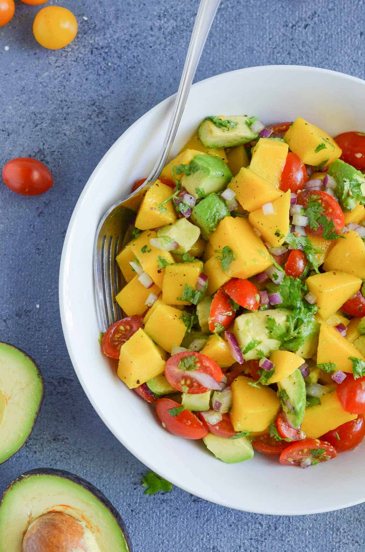 overhead click of avocado mango salad served in white bowl with fork.