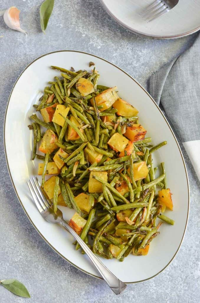 overhead click of oven-roasted potatoes and green beans served in oval platter.