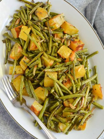 overhead click of green beans and potatoes served in grey oval plate.