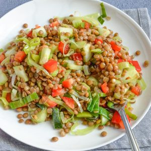 warm brown lentil salad served in white plate along with a fork.